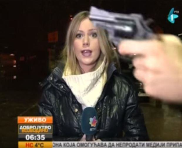news2 Man Waves Gun In Front Of Live TV Reporter, She Just Carries On Anyway