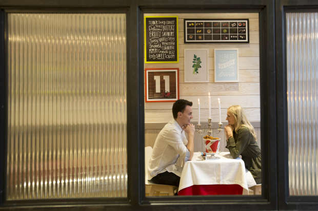 the couple enjoy the colonels hospitality as they sit deep in conversation at the date night table in kfc KFC Are Trying Out Romantic Table Service For Valentines Day