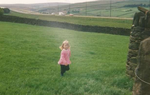 Kimberley as a child with the motorway behind her Woman Reveals What Growing Up In House In Middle Of M62 Was Like